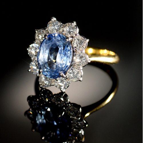 9 - <strong>A CORNFLOWER SAPPHIRE AND DIAMOND RING </strong> the oval sapphire in a surround of ten even...