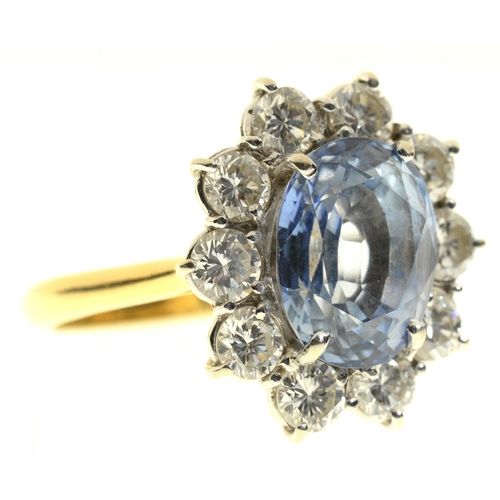 9 - <strong>A CORNFLOWER SAPPHIRE AND DIAMOND RING</strong> the oval sapphire in a surround of ten even...