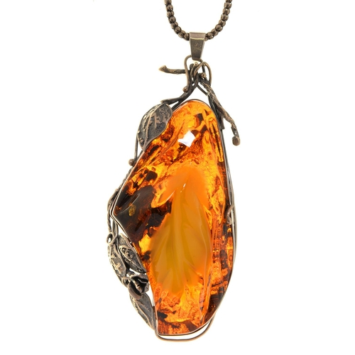 45 - AN UNUSUALLY LARGE SILVER AND LEAF CARVED AMBER PENDANT, THIRD QUARTER 20TH C, APPROX 140MM EXCLUDIN...