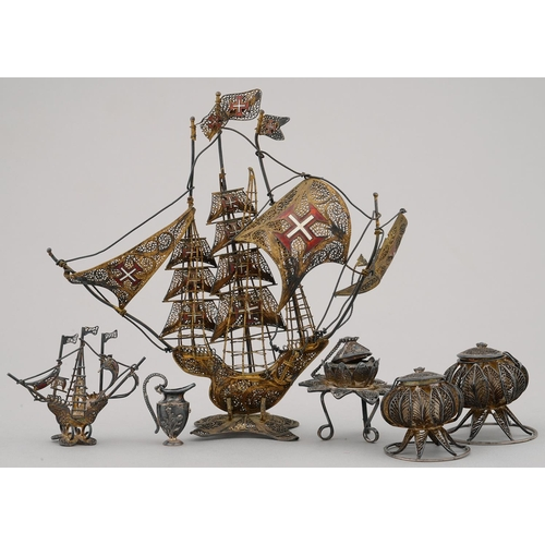 192G - A SPANISH GILT SILVER COLOURED FILIGREE AND ENAMEL MODEL OF A SHIP AND FIVE SIMILAR SMALLER ARTICLES...