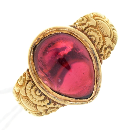 15 - A PEAR SHAPED RED STONE CABOCHON RING, ON ASSOCIATED GOLD HOOP WITH CHASED SHOULDERS, UNMARKED, 7....