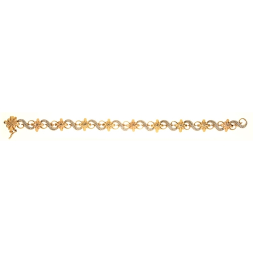 33 - A DIAMOND BRACELET OF ALTERNATE STAR AND SCROLL LINKS, IN 9CT GOLD, 19CM L, MAKER TJ, BIRMINGHAM 199...