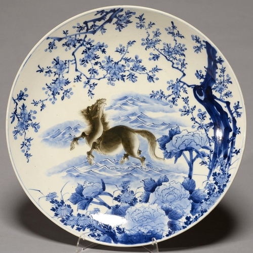 378 - A JAPANESE BLUE AND WHITE AND SEPIA IMARI CHARGER, EARLY 20TH C, PAINTED WITH A WILD HORSE BENEATH A...