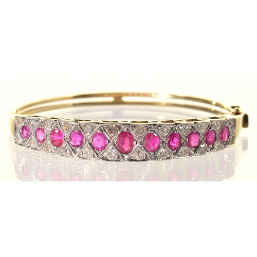 47 - A RUBY AND DIAMOND BANGLE, LATE 20TH C, THE LINE OF LARGER GRADUATED RUBIES CENTRING A DIAMOND TRELL...