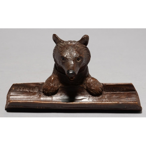 496 - A SWISS BLACK FOREST CARVED LIMEWOOD BEAR NOVELTY INKWELL AND PEN TRAY, C1930, WITH BLACK BOOT BUTTO...