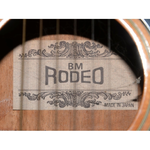 557 - AN ACOUSTIC GUITAR LABELLED B M RODEO MADE IN JAPAN...