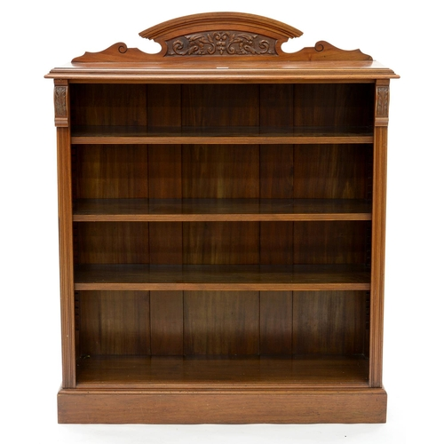 853 - AN EDWARDIAN WALNUT OPEN BOOKCASE, WITH LOW ARCHED, CARVED UPSTAND, HAVING ADJUSTABLE SHELVES FLANKE...