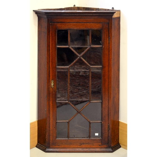 924 - A GEORGE III MAHOGANY SPLAY FRONTED HANGING CORNER CABINET, FITTED WITH STRAIGHT SHELVES ENCLOSED BY...