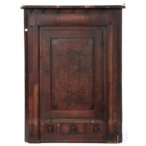 1454 - A George IV oak hanging corner cupboard, c1830, the rudimentary cornice with split ebonised pendants...