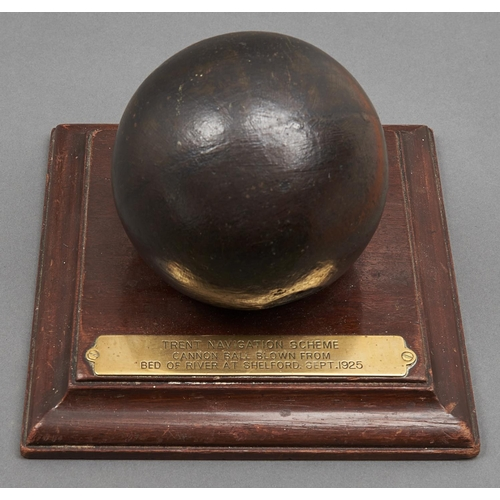 1018 - A 12cm diam cast iron cannonball, 17th c, mounted on a mahogany square plinth bearing brass plate i...