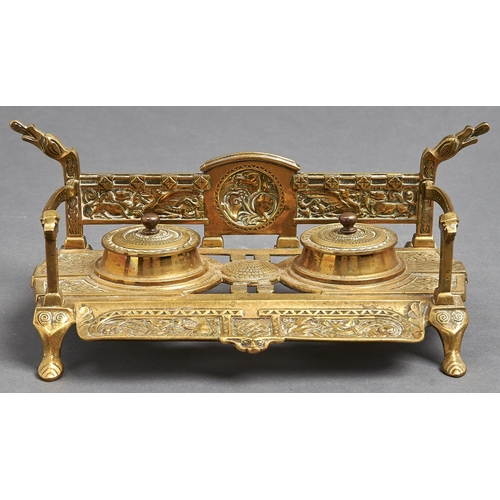 1067 - A brass inkwell of Celtic design, late 19th/early 20th c, the back with cast back centred on a round...