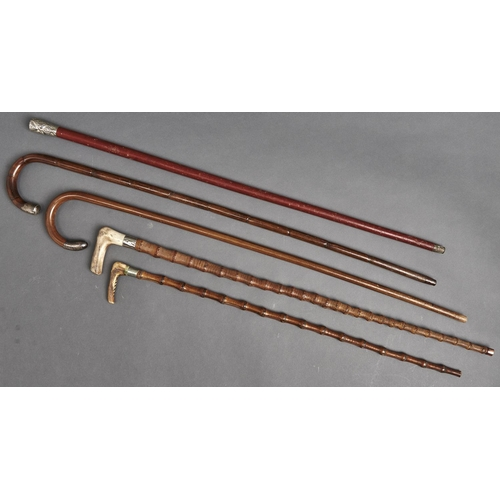 1089 - Five silver mounted and other walking canes and sticks, all c1900, three of bamboo, two with antler ...