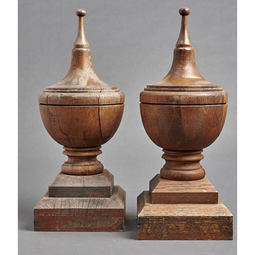 1099 - A pair of shield shaped oak finials, on stepped square chamfered base, 60cm h