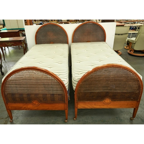 1429 - A pair of Edwardian arched and inlaid mahogany and caned single beds, c1910, with bed irons, bases a...