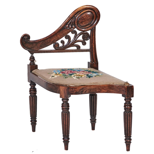 1555 - A George IV grained rosewood music stool, the half-back of boldly carved scrolling design, having pa...