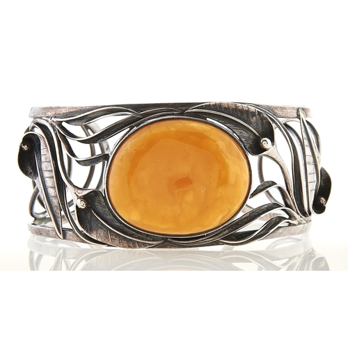 247 - A silver bangle set with large amber cabochon, 40.5g