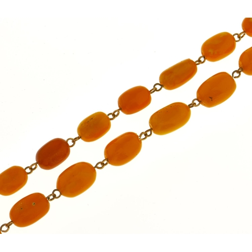 584 - A necklace of 64 amber beads, 61.7g