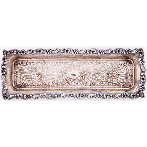 666 - An Edwardian die stamped silver comb tray, decorated with flowers, scrolls and spume, 22.5cm l, by H...