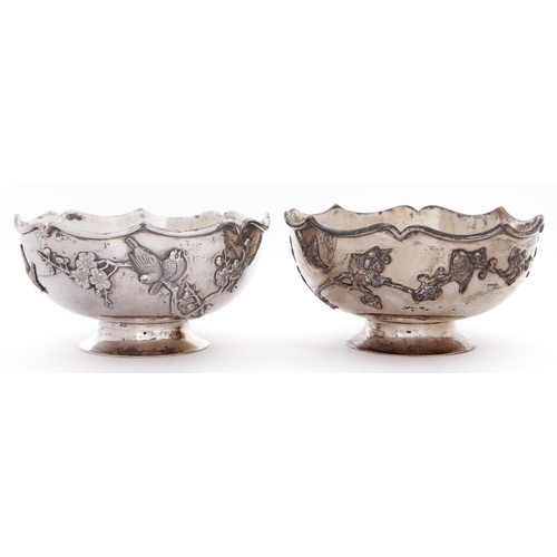 690 - A pair of Chinese silver bowls, early 20th c, applied with repousse birds and blossoming bands, on f...