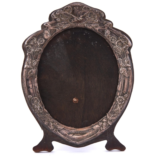 710 - An Art Nouveau silver photograph frame, the mount die stamped with insects and entrelac, backed on o...