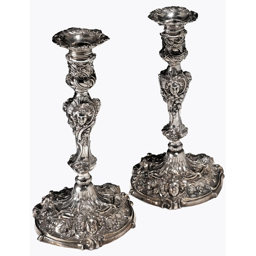 717 - A pair of George II rococo silver candlesticks, cast and chased in high relief with masks, spirallin...