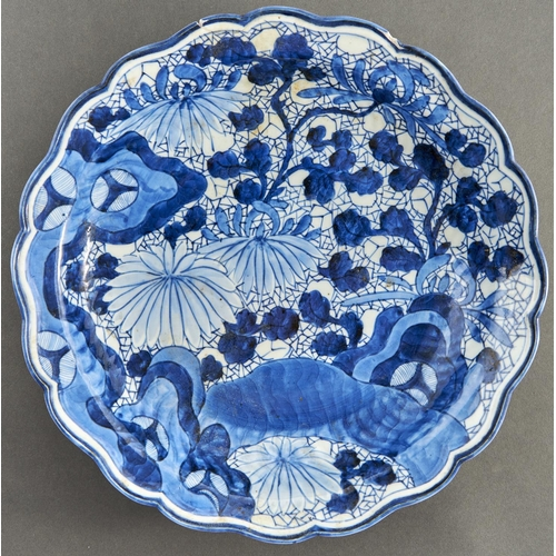 859 - A Japanese blue and white dish, Arita, 18th c, painted with flowering plants in slightly upturned, l...