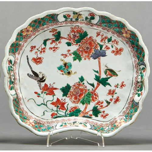 853 - A Chinese famille verte shell shaped dish, Qing dynasty, Kangxi period, painted with a tree peony an...