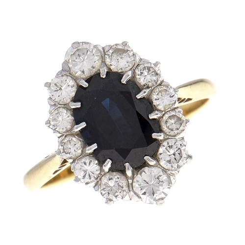 503 - A sapphire and diamond cluster ring,the larger dark blue sapphire within a surround of 12 round bri...