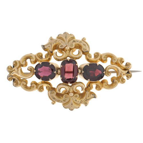 512 - A Victorian garnet brooch, c1870, in gold, formed of c scrolls and leafage, 55mm l, 10.6g...
