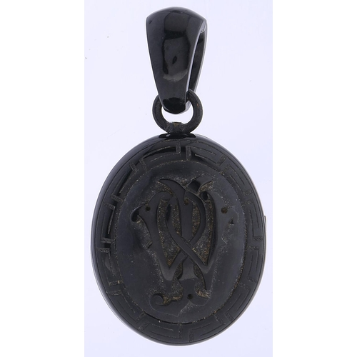 526 - A Victorian jet mourning locket, c1870, carved with a monogram within Greek key border, 70mm overall...