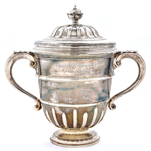 42 - Racing Trophy. A George V silver cup and cover,of urnular form, with ogee domed cover and leaf capp...