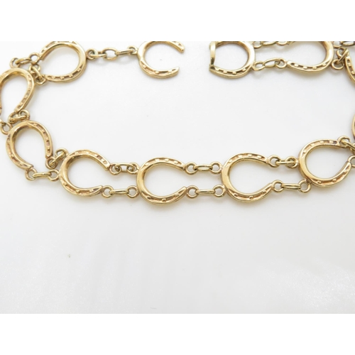 23 - 9ct gold HM bracelet of lucky horseshoes 9.5g