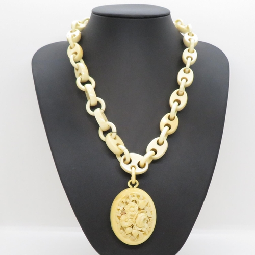 57 - Early Victorian carved ivory locket and fancy ivory chain 51cm length, pendant is 5cm by 4cm