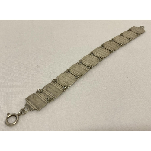 34 - An Art Deco silver link bracelet with engine turned detail.  Stamped 'silver' to reverse.  Approx. 7...