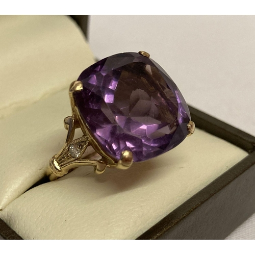 5 - A 9ct gold amethyst and diamond dress ring with large cushion cut central amethyst.  A small round c...