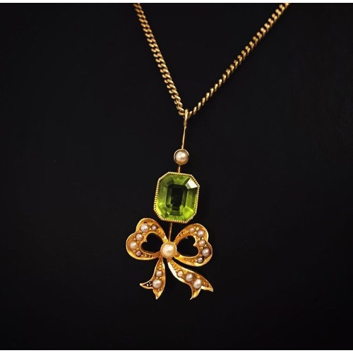 5 - An antique 18ct gold peridot and seed pearl pendant with bow detail on a 14ct gold fine curb chain. ...