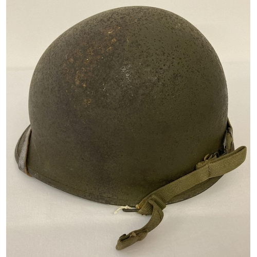 1038 - Original US M1C WW2 Paratrooper helmet - 1944 specification, rear join. Complete with helmet chinstr...