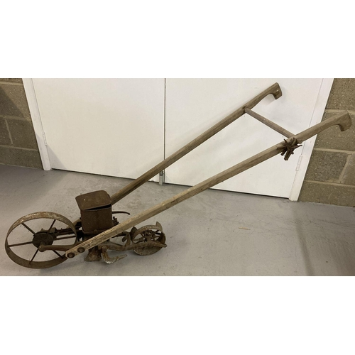 1405 - An American planet Jnr No. 4 wooden handled seed drill with cast metal wheels.