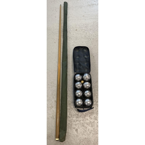 1253 - A wooden snooker cue with protective sleeve. Together with a set of metal Boules by Nauticalia, Lond...