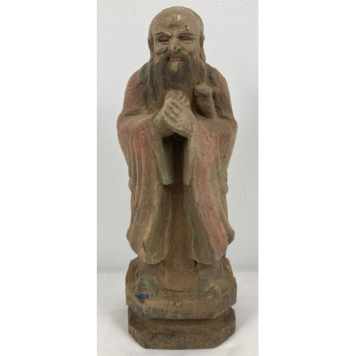 1119 - An Oriental carved wooden figure with painted detail. Approx. 26cm tall.