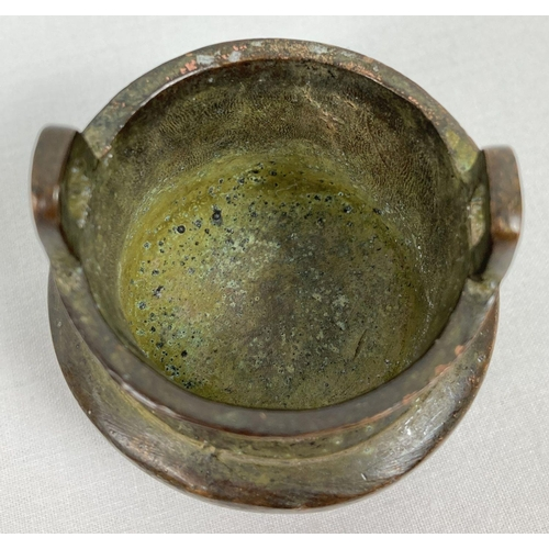 1122 - A miniature Chinese bronze censer with loop handles and raised on tapered tripod legs. Impressed mar...