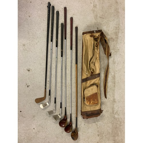 1258 - A vintage canvas and leather pencil golf club bag with a collection of vintage golf irons and woods....