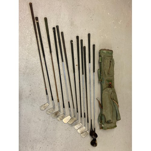 1260 - A vintage green canvas Bryant pencil style golf club bag with a collection of vintage irons and wood...