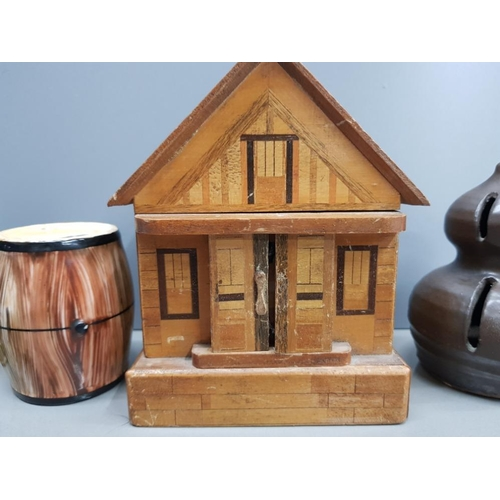 41 - A COLLECTION OF 5 MONEY BOXES TO INCLUDE A BRASS MILK CHURN,  A WOODEN CHALET WITH KEY, A STUDIO POT...