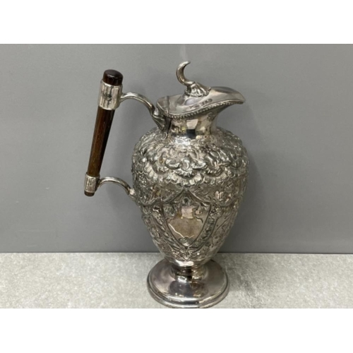 """52 - 9.5"""" heavily embossed claret jug circa 1890 with vacant shield cartouche either side, Ebony handle s..."""