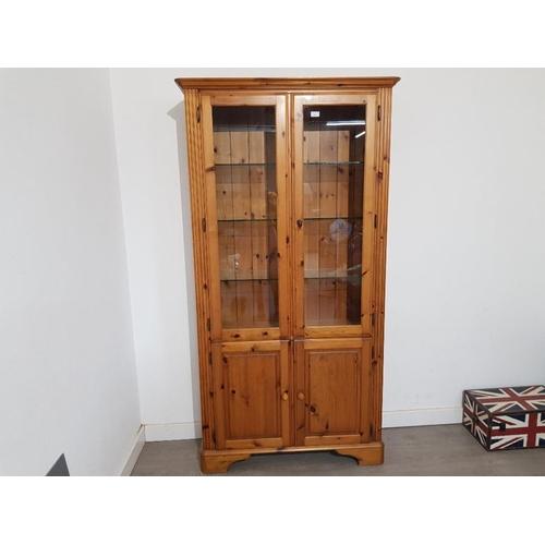 A modern pine display cabinet with lights, cupboard doors below 98 x 188.5 x 31cm