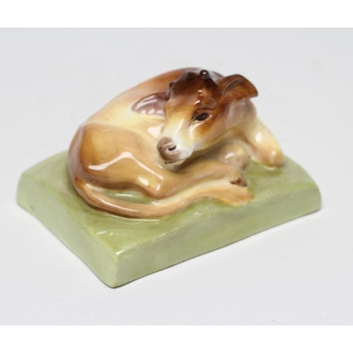 49 - A ROYAL WORCESTER CHINA CALF, 1931, designed by Stella Crofts and modelled recumbent on an oblong ba...