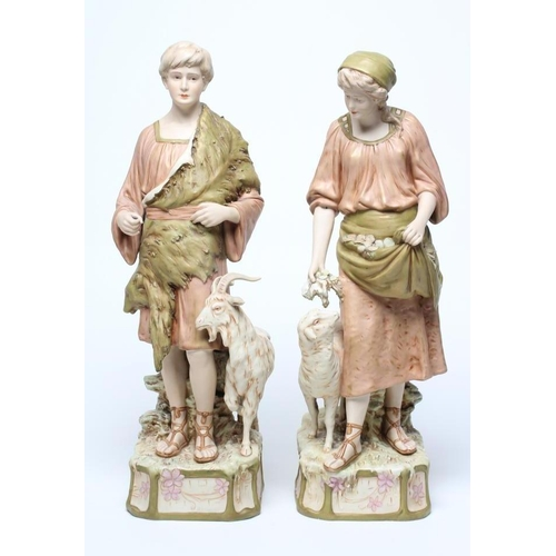 54 - A LARGE PAIR OF ROYAL DUX BISQUE PORCELAIN FIGURES, early 20th century, modelled as a young goatherd...