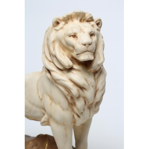 55 - A ROYAL DUX BISQUE PORCELAIN LION, early 20th century, modelled standing on a rocky outcrop, pink pa...