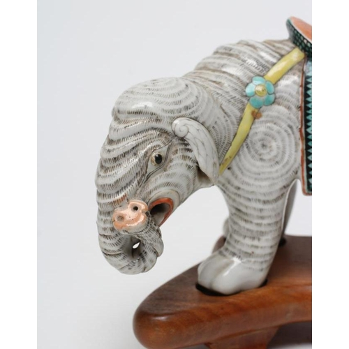 7 - A CHINESE PORCELAIN JOSS STICK HOLDER/INCENSE BURNER modelled as an elephant with orange, green and ...